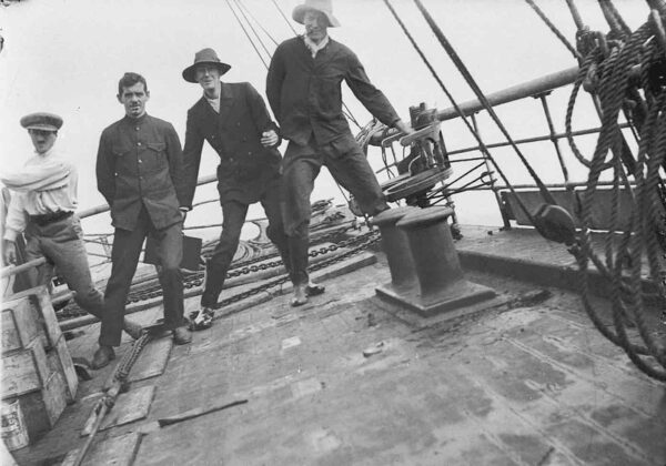 Four men leaning on the shifting deck of the Aurora.