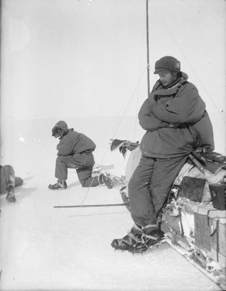 A man leaning against a sledge, eyes closed