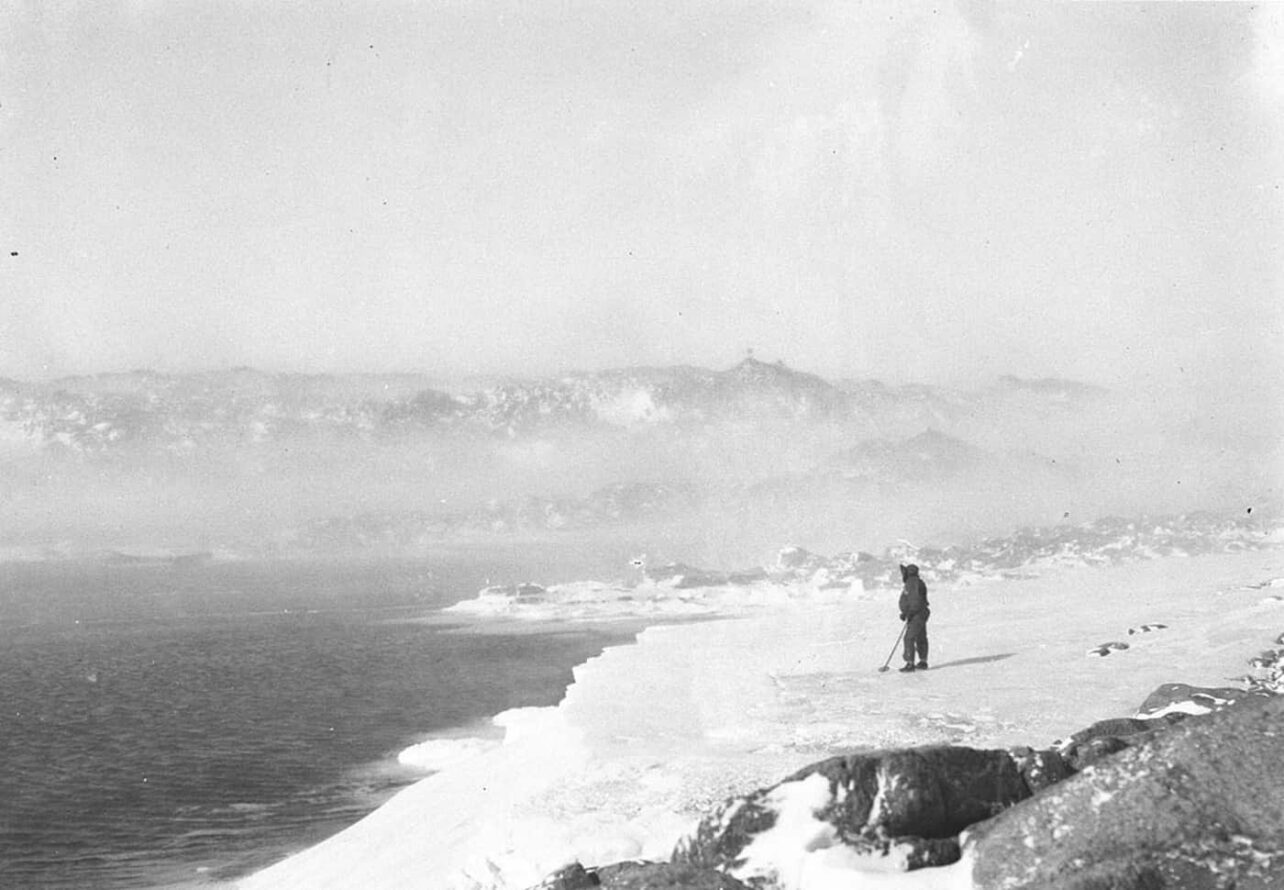 A man, Mertz, standing on the coast of Cape Denison, drfting snow making landscape fuzzy