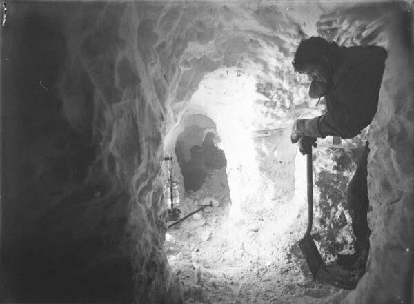 A man leaning on his shovel in an underground ice tunnel.