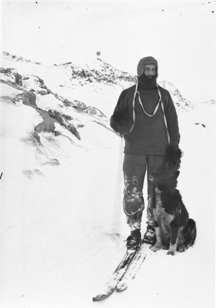 A man on skis with a seated dog on his left