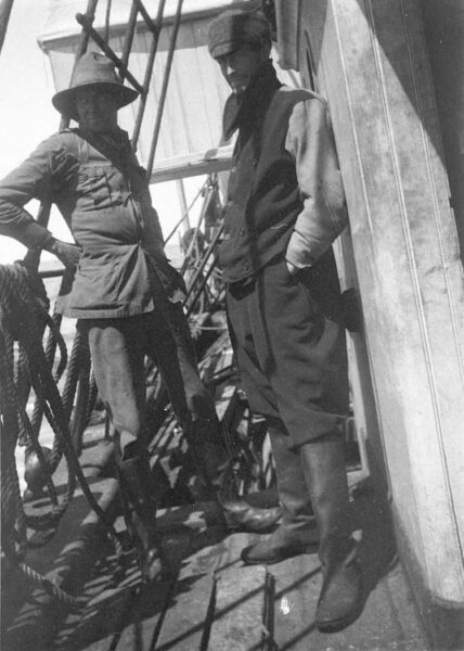 Two men on board a ship looking at camera