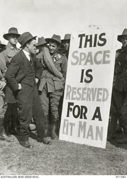 Australian soldiers on a recruitment drive encourage a man to enlist. The poster reads: THIS SPACE IS RESERVED FOR A FIT MAN.
